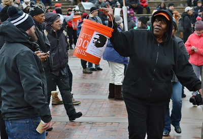 Woman collecting donations with large bucket at MLK Day rally in Denver.