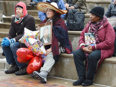 Woman wearing a sombrero and holding a picture of Martin Luther King, listens to rally speakers.