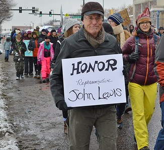 Man in MLK Day march holding sign about Rep John Lewis.