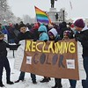 Group of young marchers holding banner, waiting in the snow for MLK Day march to begin.