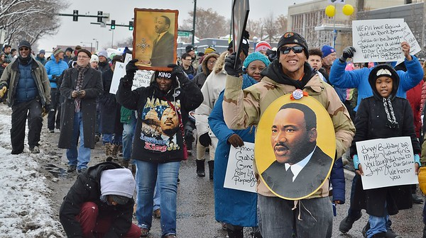 MLK Day attendees marching with signs in the snow.