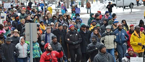MLK Day marchers linking arms, including US Senator Michael Bennet, Denver Mayor Michael Hancock, Colorado Governor John Hickenlooper, and former Denver Mayor Wellington Webb.