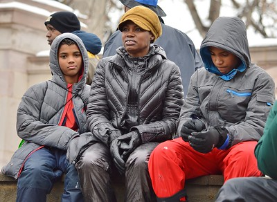 Mother and two children listen to speakers at MLK Day event in Denver.