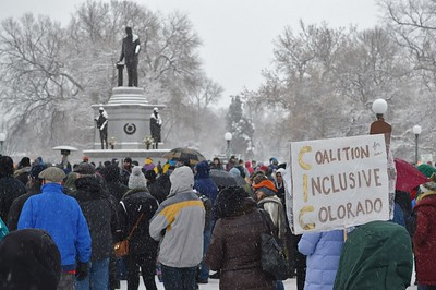 Crowd of marchers huddles in the cold below statue of Martin Luther King.