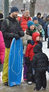 Parents and their children wait in the snow for MLK Day parade to start.