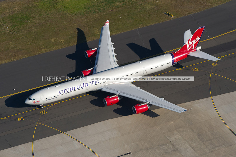 One of Virgin Atlantic's Airbus A340-600 aircraft with the older colour scheme (registered G-VYOU) is seen here taxiing out to runway 34L at Sydney airport. The overhead view makes the length of the A340-600 more evident.