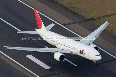 Japan Airlins B777-200/ER from Tokyo landing on runway 34 left at Sydney airport. Seen from the air.