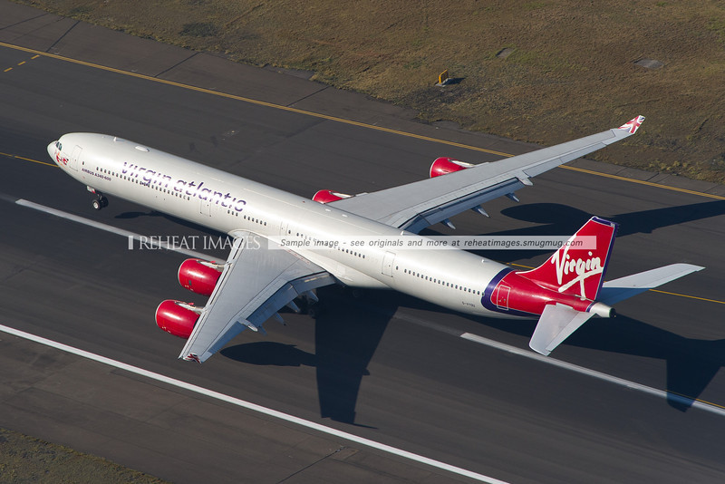 One of Virgin Atlantic's Airbus A340-600 aircraft with the older colour scheme (registered G-VYOU) is seen here heading down runway 34 left at Sydney airport and is just starting to lift off.