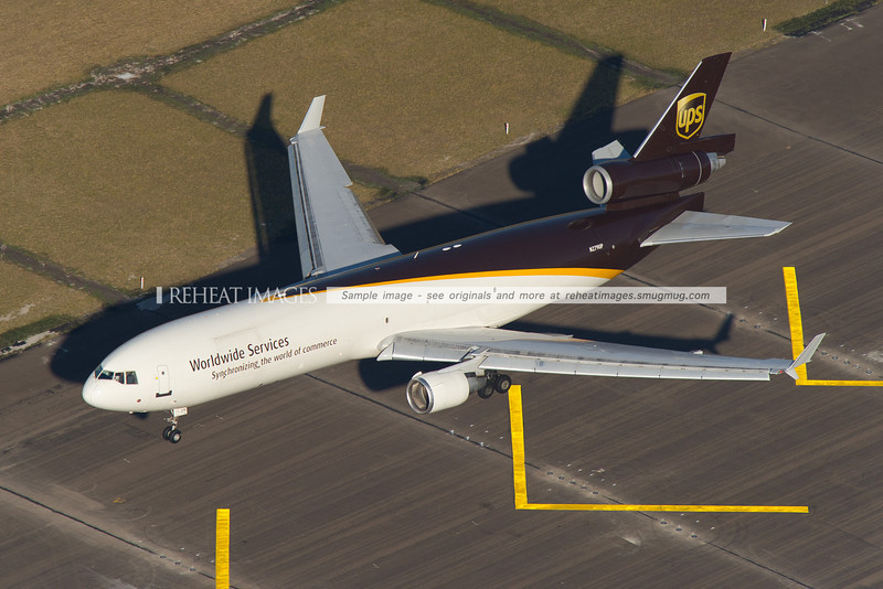 An overhead view of a UPS McDonnell Douglas MD-11F landing at Sydney Airport on runway 34L.