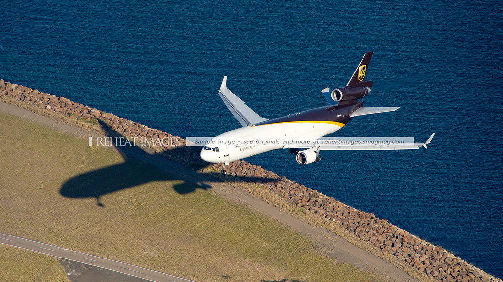 An overhead view of a UPS McDonnell Douglas MD-11F approaching Sydney Airport runway 34 left. Here it is seen as it crosses above the sea wall.