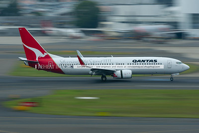 """A Qantas Boeing 737-838 lands at Sydney airport. The plane wears a special motif """"Sharing the Spirit""""."""