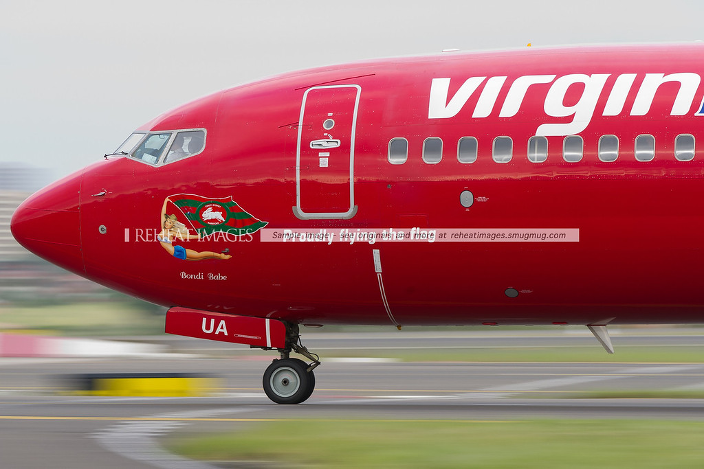 Virgin Blue Boeing 737 VH-VUA passes by the air traffic control tower at Sydney airport. It wears the flag of the South Sydney Rabbitohs football team. A low shutter speed has blurred the background and foreground details in this image.