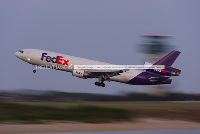 FedEx MD-11F taking off at Sydney Airport. The blurred shape in the background is the air traffic control tower.