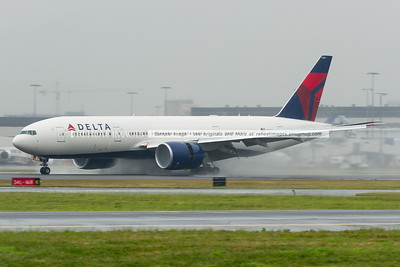 It's raining in Sydney on this day - the Delta 777-200/LR using reverse thrust throws up lots of water around and ahead of its GE-90 engines.