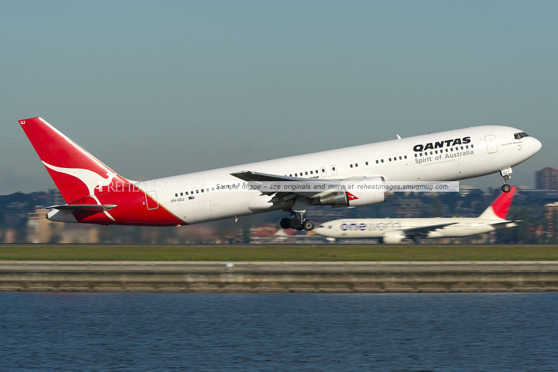 A Qantas Boeing 767-338/ER takes off from runway 34 right at Sydney airport, while Japan Airlines JA707J, a 777-246/ER in OneWorld colours is seen heading out to runway 34 left.