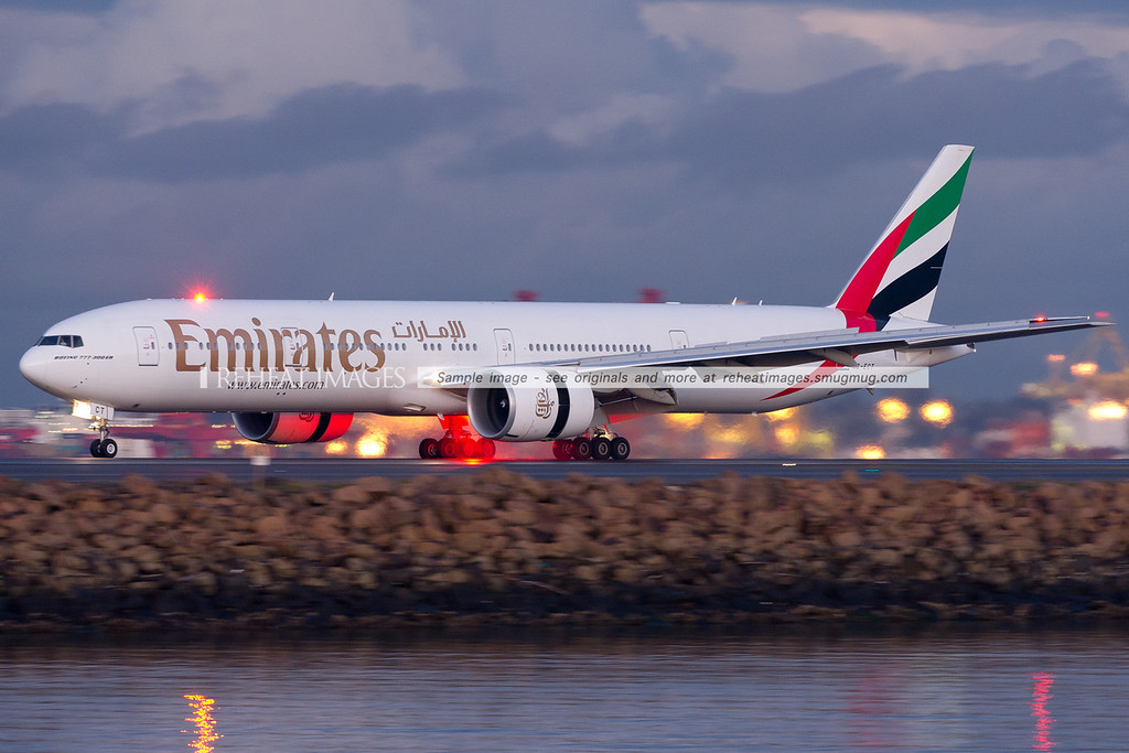 Emirates B777-300/ER lands at Sydney airport. The beacon on the plane has illuminated rain thrown up from the runway by the reverse thrust of the engines.