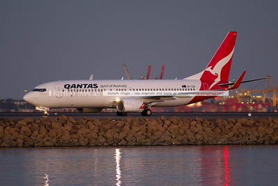 """A Qantas JetConnect B737-838 seen at dusk after landing at Sydney airport. This one is named """"Sir William Hudson"""", after Sir William Hudson, the New Zealand born engineer who was the first Commissioner of the Snowy Mountains Hydro Electric Authority in Australia between 1949-1967."""