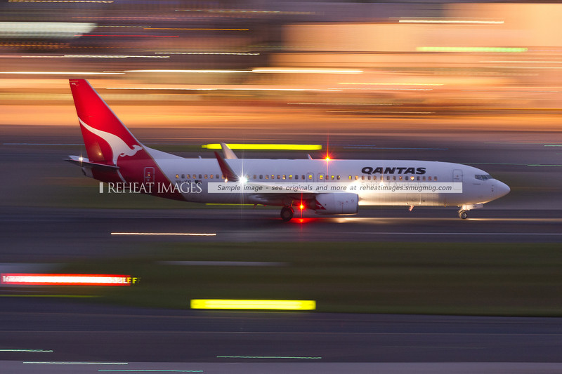 A Qantas Boeing 737-838 takes off from Sydney airport at dusk.