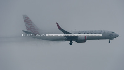 A Virgin Australia Boeing 737 lands at Sydney in very heavy fog. It trails vapour from around the edges of the flaps and condensation from over the wing.