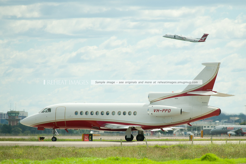 Paspaley's Dassault Falcon 900 waits for takeoff clearance, while a QantasLink Dash 8 Q400 takes off in the background.