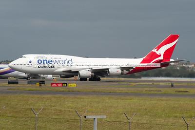Qantas Boeing 747-438 departs Sydney airport. VH-OJU carries the OneWorld alliance titles.