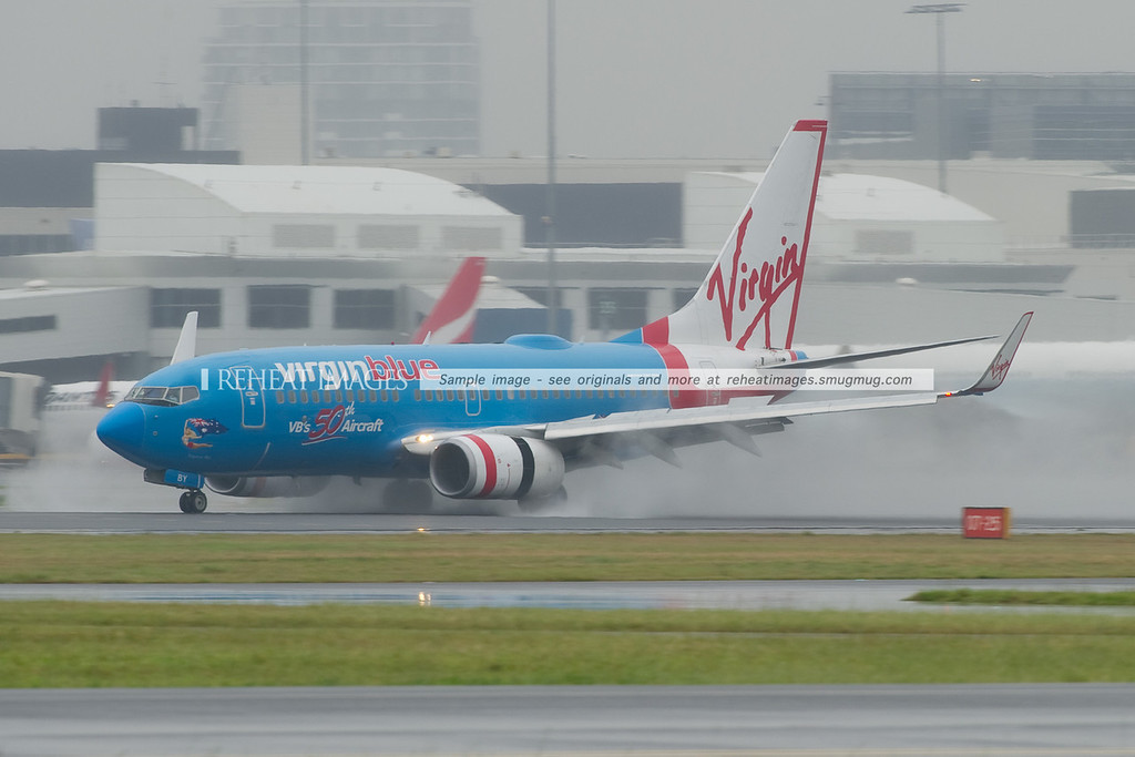 "Virgin Blue (Virgin Australia) ""Virginia Blue"", the only blue coloured B737 in their fleet lands at Sydney airport on a very wet Thursday morning."
