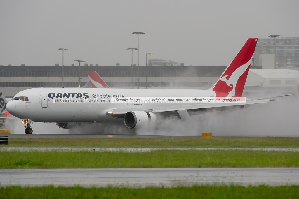 Qantas Boeing 767-338/ER slows down on a very wet runway 16 right at Sydney airport.