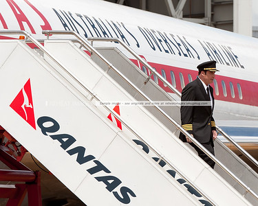 John Travolta descends down the stairs from his 1964 Qantas Boeing 707-138B at the Qantas 90th anniversary celebrations in Sydney.