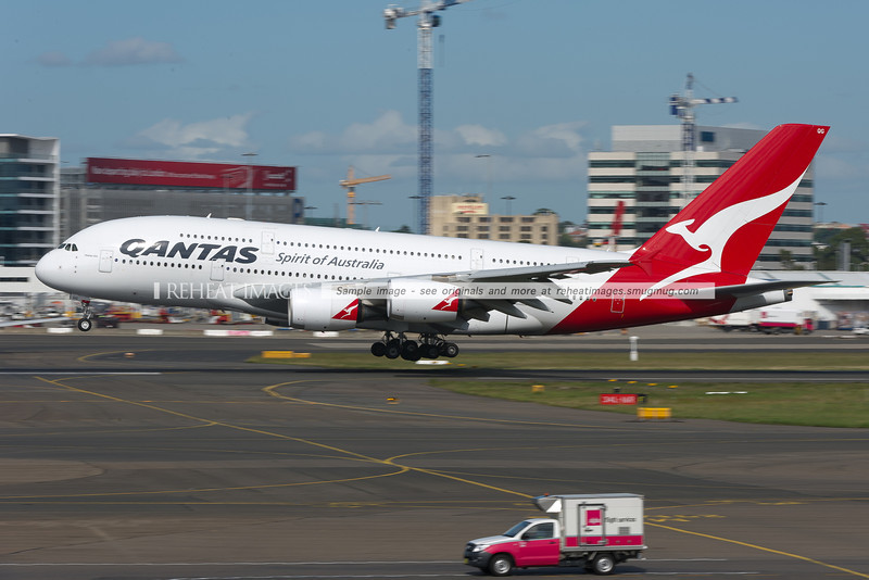 Qantas Airbus A380 lands at Sydney airport. The Alpha Flight Services Toyota in the foreground is a stark contrast in size.