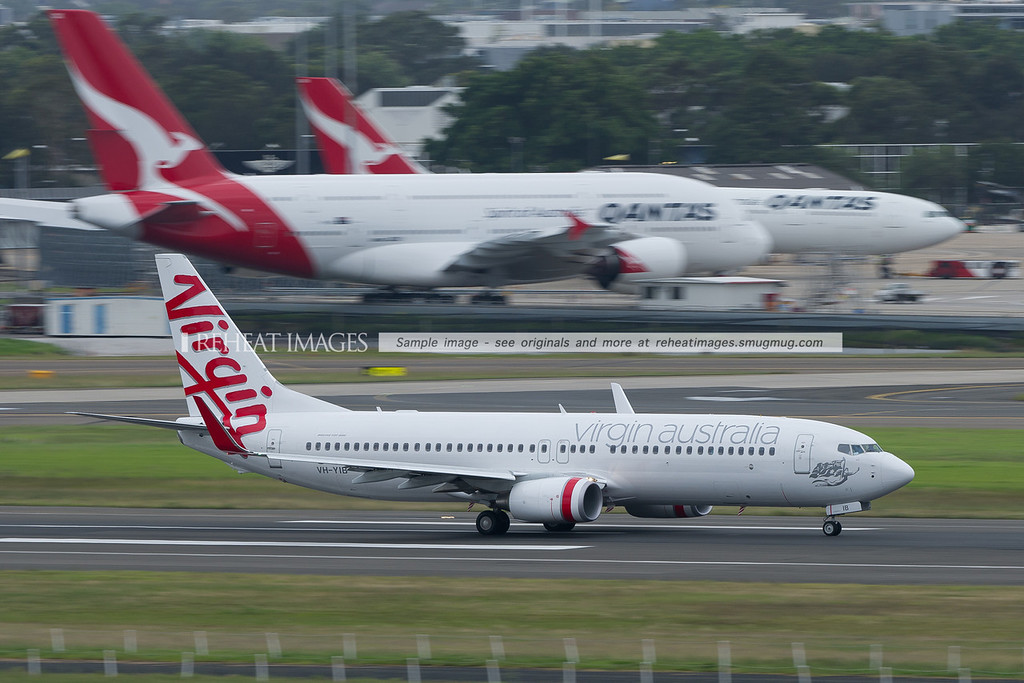 A Virgin Australia B737-800 takes off from Sydney airport. Qantas Airbus A330 and A380 are visible in the background.