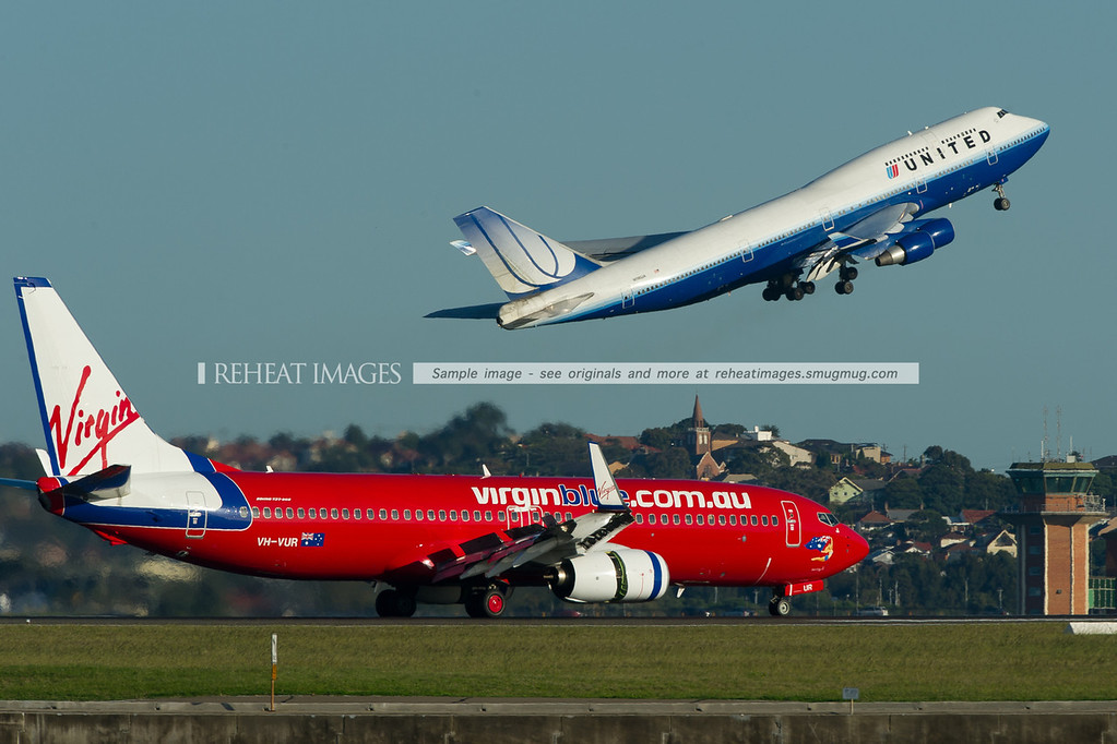 A Virgin Blue Boeing 737-800 lands on runway 34 right at Sydney airport, while a United Airlines B747-422 takes off from runway 34 left, leaving for Melbourne. The United plane uses only a small portion of the long runway, The B747's steep climb seen here gives a clue to its light weight.