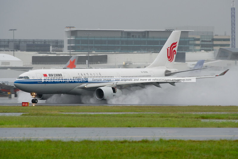 Air China Airbus A330-300 slows down on runway 16 right at Sydney airport. The thrust reverse is throwing up plenty of standing water from the runway.