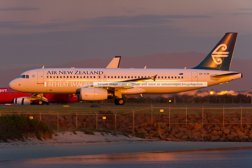 Air New Zealand Airbus A320 at Sydney airport, lit by the sunset.