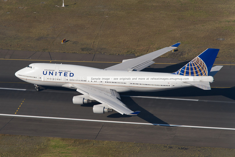 A United Airlines Boeing 747-422 lifts off from runway 34 left at Sydney Airport. It is seen here from above, looking towards the east.