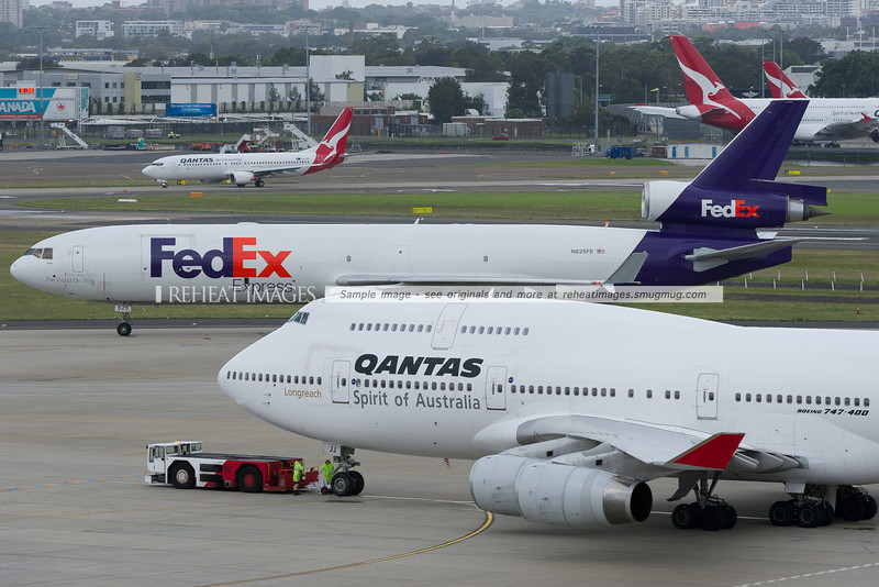 A Fedex McDonnell-Douglas MD-11F taxies  to the cargo ramp while a Qantas B747-438 VH-OJJ is pushed back, and a B737-838 waits in the background for takeoff clearance.