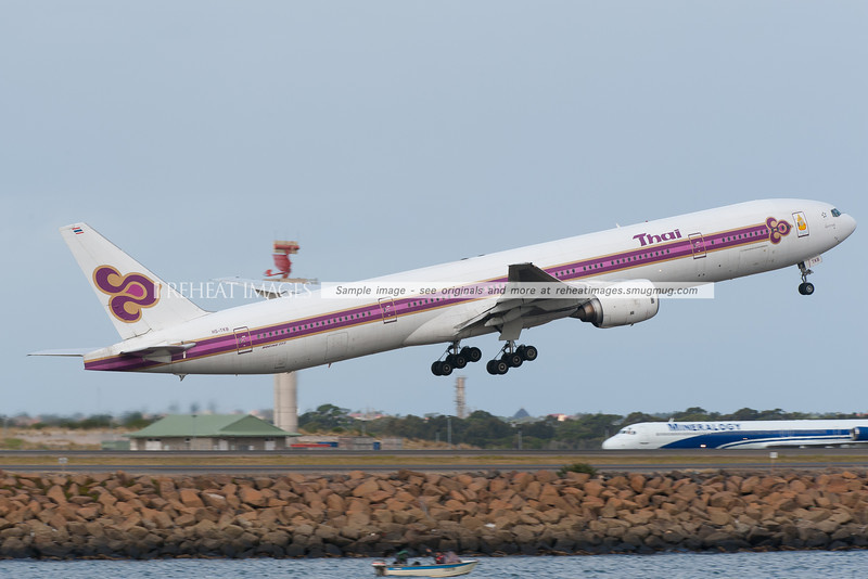 A Thai Boeing B777-300 takes off from Sydney airport. At the time of this photo, it was still wearing the classical colour scheme of the airline. A Mineralogy McDonnell-Douglas is seen in the background.
