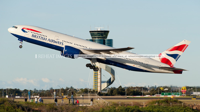 A British Airways Boeing 777-236/ER takes off from Sydney airport. A group of plane spotters are visible against the fence line, with cameras in hand.