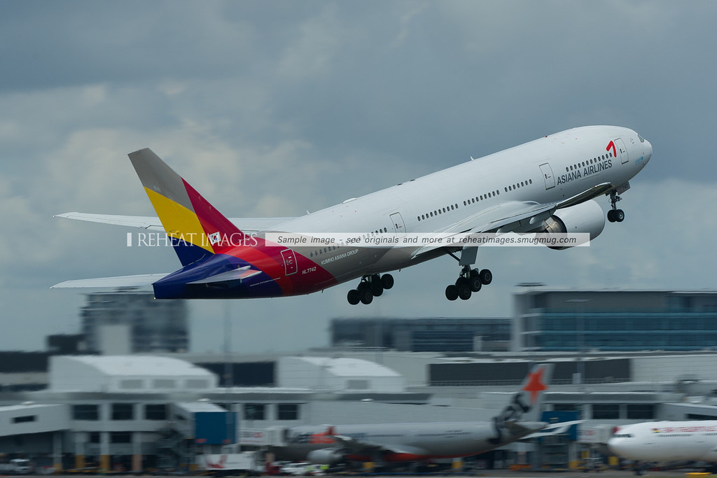 Asiana Boeing 77728E/ER leaves Sydney during a temporary and light rain shower.
