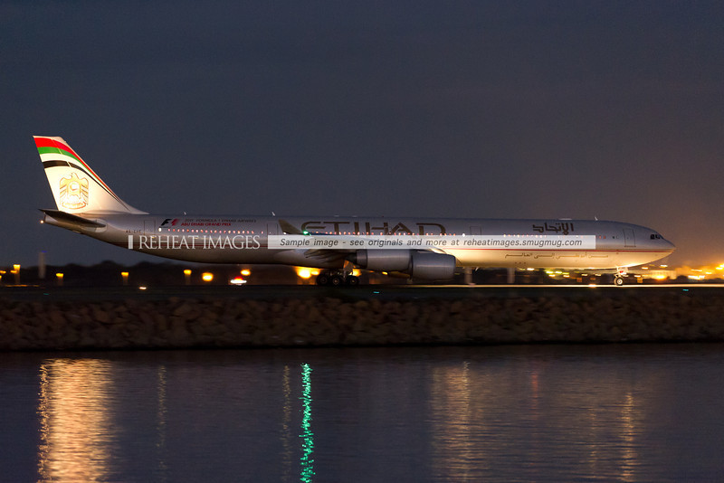 Etihad A340-642 arrives at Sydney airport at night.