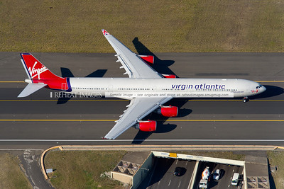 One of Virgin Atlantic's Airbus A340-600 aircraft with the older colour scheme (registered G-VYOU) is seen here taxiing out to runway 34L at Sydney airport. Here it is crossing over General Holmes Drive.