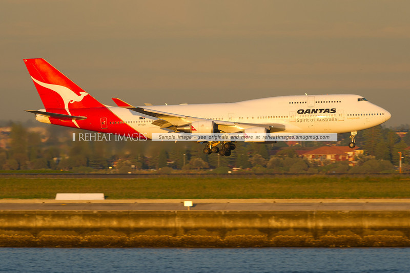 A Qantas Boeing 747-438/ER is landing at Sydney airport runway 34 left against the backdrop of Brighton-Le-Sands. The plane is powered by four General Electric CF6-80C2-B5F engines.