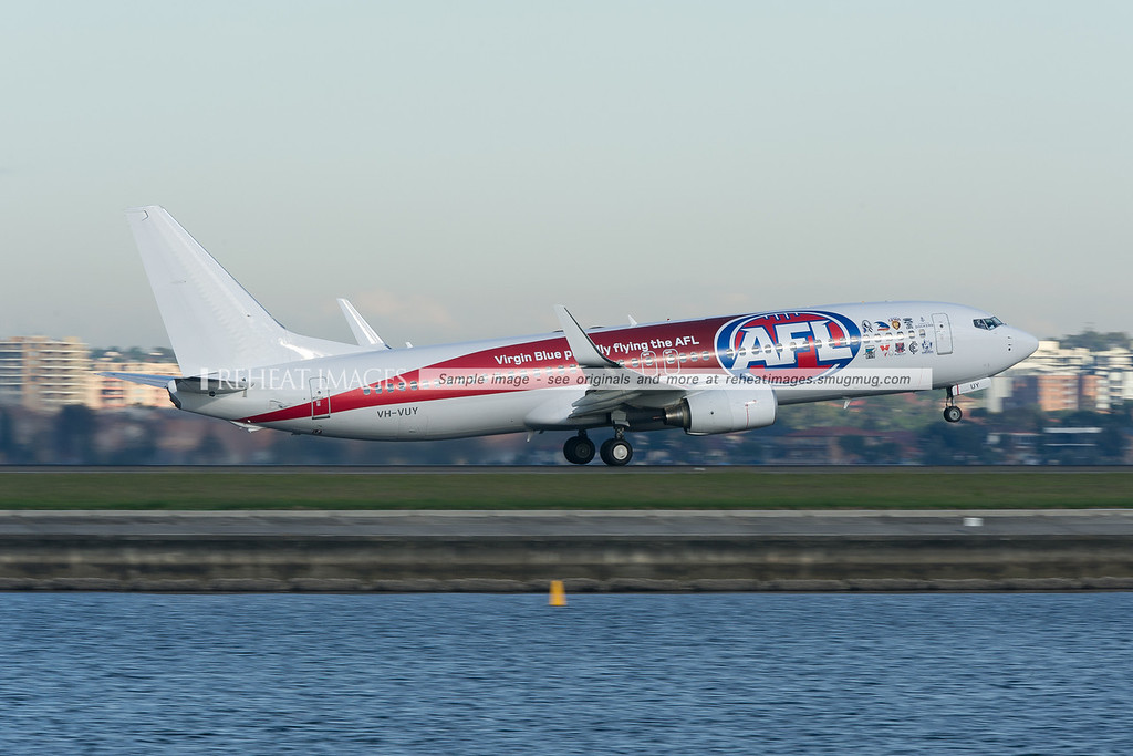 A Virgin Blue Boeing 737-800 takes off from runway 34 right at Sydney airport. This plane carries the AFL colour scheme.