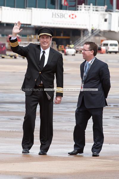 A waving John Travolta and Qantas' Alan Joyce at the Qantas 90th anniversary celebrations in Sydney.