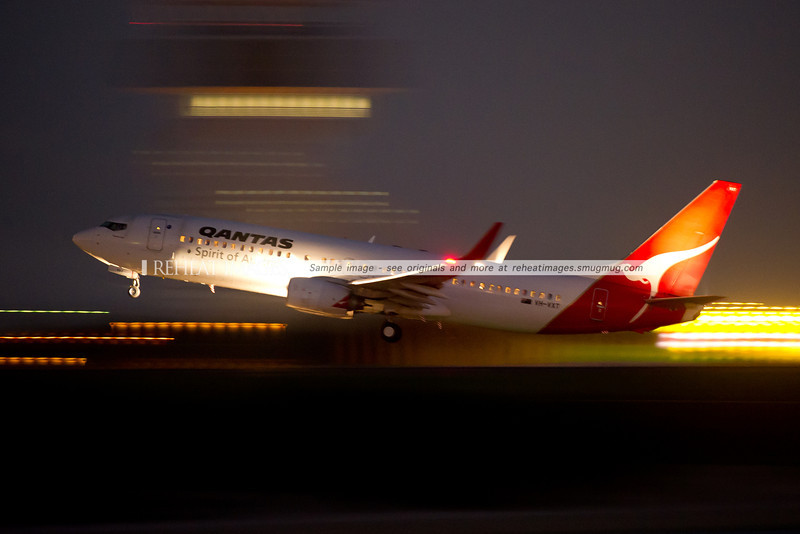 A Qantas Boeing 737-838 takes off from Sydney airport at night. The high speed of the plane and the slow shutter speed have rendered all foreground and background details into streams of light.