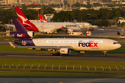 A Fedex McDonnell Douglas MD-11F leaves Sydney airport on runway 16 right at sunset. In the background is the ramp area of the Qantas jetbase. the A380-842 is VH-OQC. At the time of this photograph, some engines were removed temporarily.
