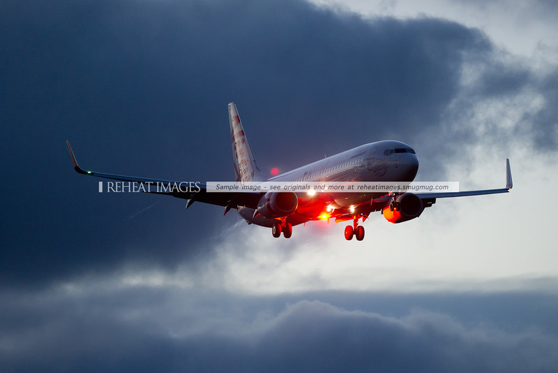 A Virgin Australia Boeing 737-800 approaches Sydney airport at dusk.
