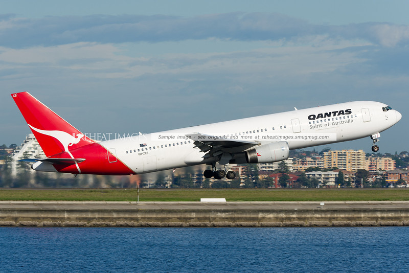 A Qantas Boeing 767-336/ER VH-ZXB departs Sydney airport on runway 34 right. Brighton-Le-Sands is seen in the background.