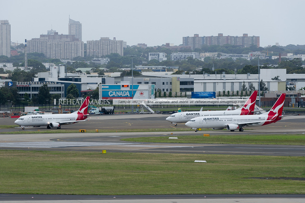 3 Qantas B737 planes wait for takeoff clearance at Sydney airport. The left plane is a B737-476, while the others are the 838 version.