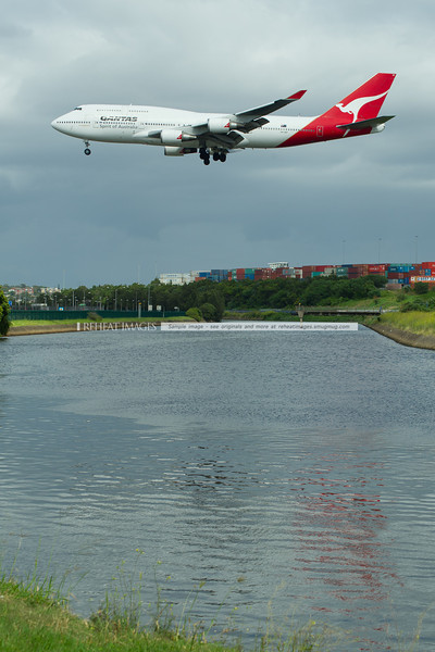 A Qantas Boeing 747-438/ER approaches runway 16 right at Sydney airport, crossing over the canal beside Qantas Drive.