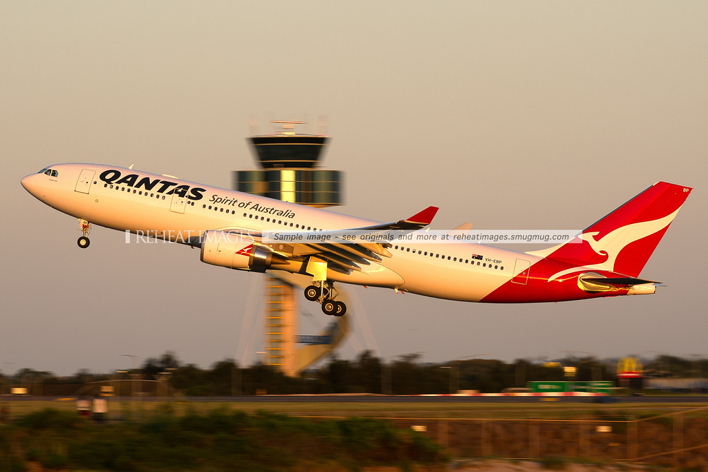 A Qantas Airbus A330-202 departs Sydney airport on runway 34 left - passing in front of the air traffic control tower.